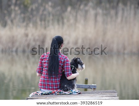Pretty young girl hugging her dog on the wooden dock on the river. Rear view of the girl with long black hair and miniature schnauzer - stock photo