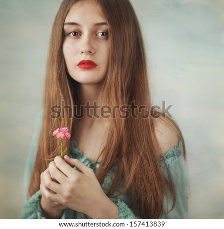 Pretty young girl in a blue dress with a flower. - stock photo