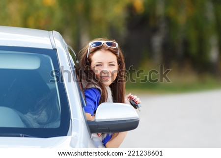 pretty young girl in a car - stock photo
