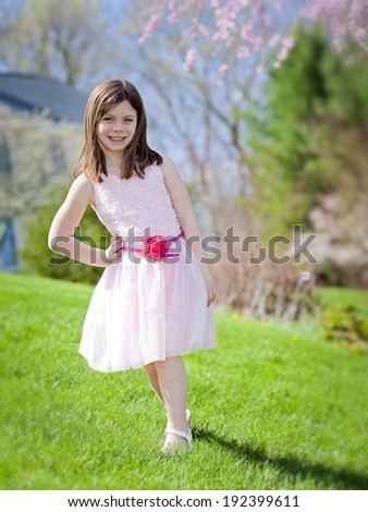 Pretty young girl in a pink dress outside during spring - stock photo