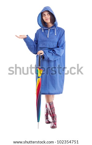 Pretty young girl in a raincoat and umbrella checks to see if it is raining - stock photo