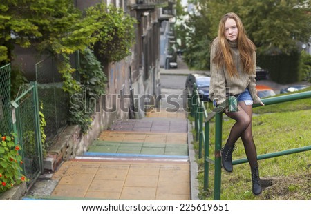 Pretty young girl in a sweater sitting on a railing street stairs. - stock photo