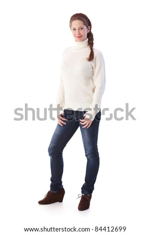 Pretty young girl in jeans and sweater smiling at camera.? - stock photo