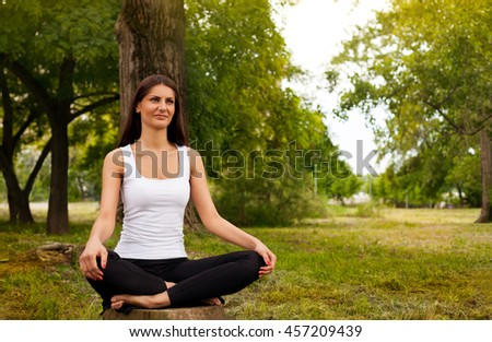 Pretty young girl in lotus pose in the park