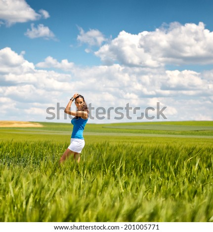 Pretty young girl in white summer shorts standing sideways in a green wheat field under a blue sky with clouds