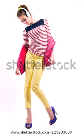 Pretty young girl isolated on white wearing bright casual clothes like yellow pants, stripped red white and blue shirt, pink vest,  purple high heels, listening to music via headphones and dancing. - stock photo