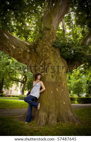 Pretty young girl lay on tree - stock photo