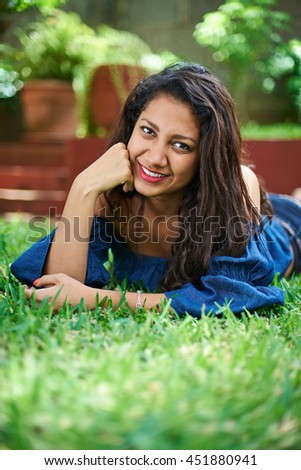 pretty young girl laying on grass in park