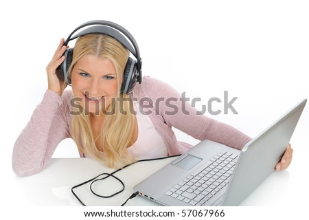 Pretty young girl listening and singing to the music with headphones from her laptop. isolated on white background - stock photo
