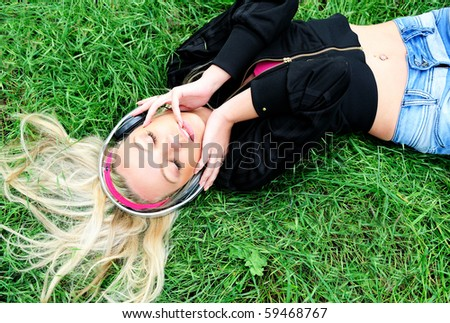 Pretty young girl listening music - stock photo