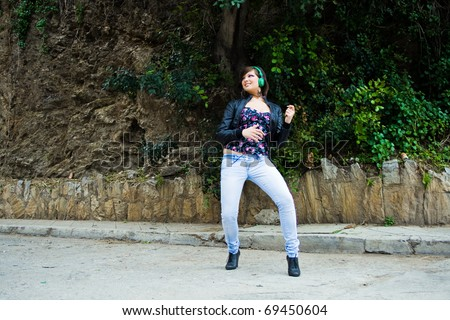 pretty young girl listening music with enthusiasm - stock photo