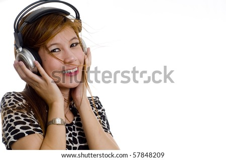Pretty young girl listening to music on headphones - stock photo