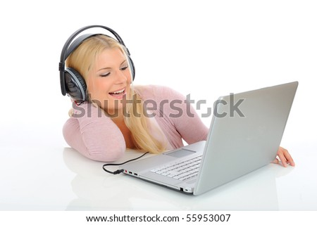 Pretty young girl listening to the music with headphones from her laptop. isolated on white background - stock photo