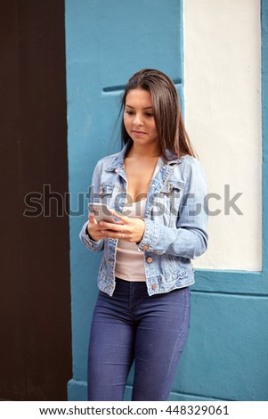 Pretty young girl looking at her cell phone while leaning against a blue wall with a white niche and smiling in casual clothing