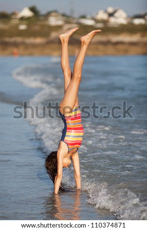 pretty young girl makes a handstand at the beach