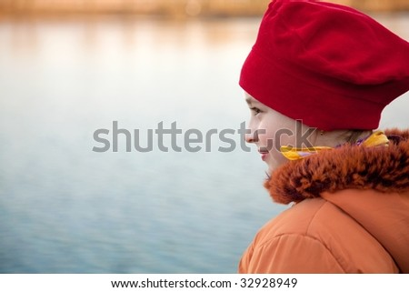Pretty young girl on lakeside - stock photo