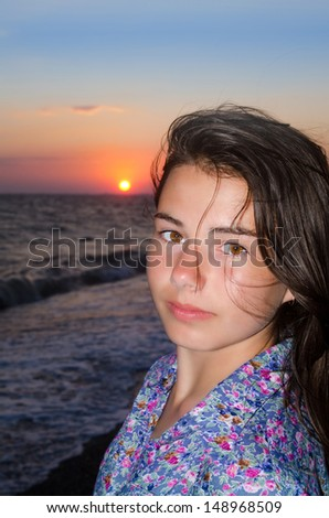Pretty young girl on the beach at sunset background - stock photo