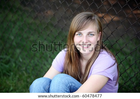 pretty young girl outside by fence - stock photo