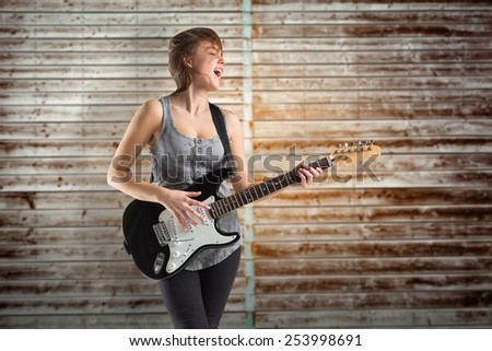 Pretty young girl playing guitar against wooden planks - stock photo
