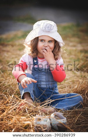 Pretty young girl playing in the street. Child's outdoor fun. Beautiful baby smile. Awsome summer day. Fancy hut, curly hair. Happy laughing kid's face. Little coquette. Minx enjoying a game portrait  - stock photo