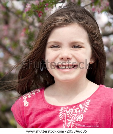 Pretty young girl portrait outdoors int he blossoms