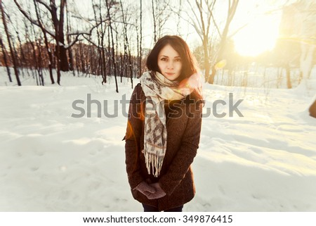 Pretty young girl posing in winter forest