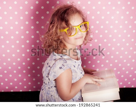 Pretty young girl reading book over pink background. Child looking at camera.