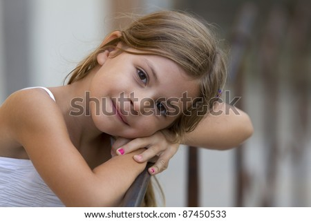 Pretty young girl resting her head on her hands and smiling