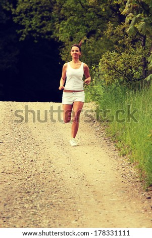 Pretty young girl runner in the forest.