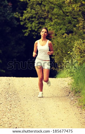 Pretty young girl runner in the forest. - stock photo