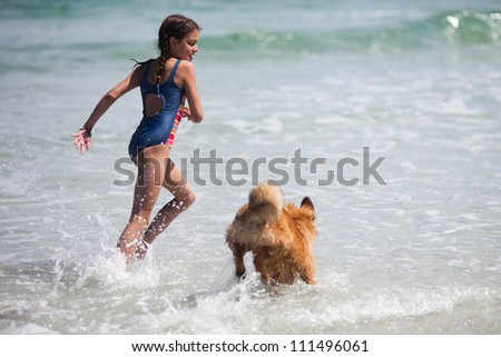 pretty young girl runs with an Elo puppy in the sea - stock photo