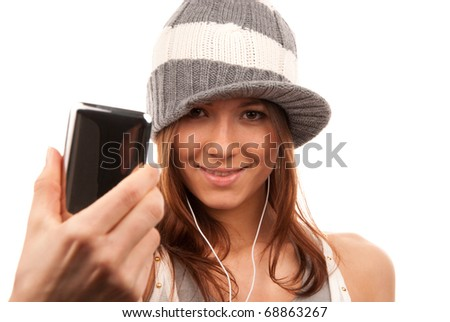 Pretty young girl showing cellular mobile phone and smiling in headphones and hat isolated on a white background