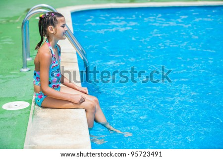 Pretty young girl sit at pool's edge - stock photo