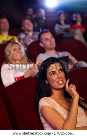 Pretty young girl sitting in multiplex movie theater, watching movie, playing with chewing gum. - stock photo