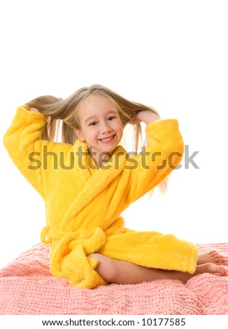 Pretty young girl sitting on a bed and touching her hair - stock photo