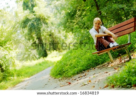 Pretty young girl sitting on a bench in the forest. - stock photo