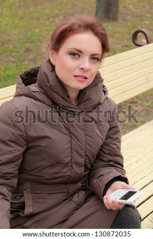 Pretty young girl sitting on a park bench and keep your mobile phone