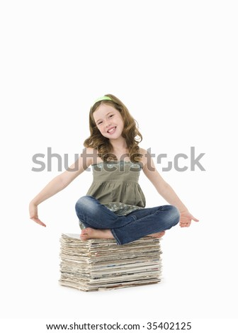 Pretty, young girl sitting on pile of old newspapers