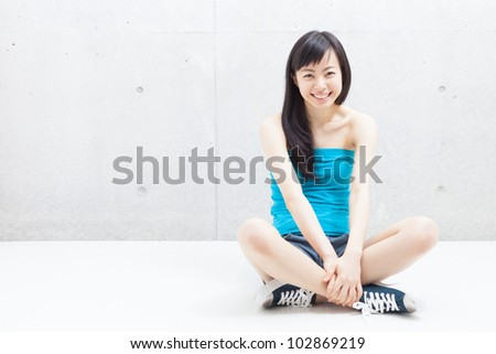 Pretty young girl sitting on the floor - stock photo