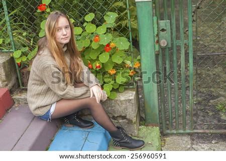 Pretty young girl sitting on the steps near the country house. - stock photo