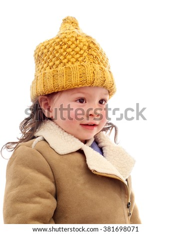 Pretty Young Girl Smiling Wearing a Coat and Wool Hat - stock photo