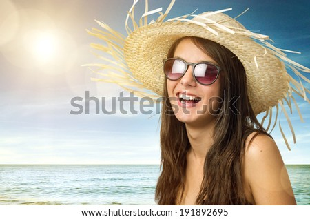 Pretty young girl smiling with straw hat and sun glasses in the beach - stock photo