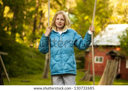 Pretty young girl standing on swing
