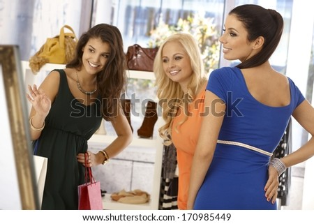 Pretty young girl trying on blue dress at clothes store, female friends looking at her, all smiling happy. - stock photo