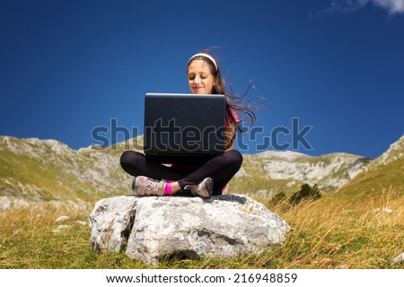 Pretty young girl using a laptop on a rock in the mountains - stock photo