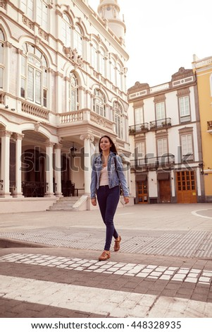 Pretty young girl walking towards camera while looking away expectantly with a toothy smile and wearing casual clothing and a backpack, old buildings behind her