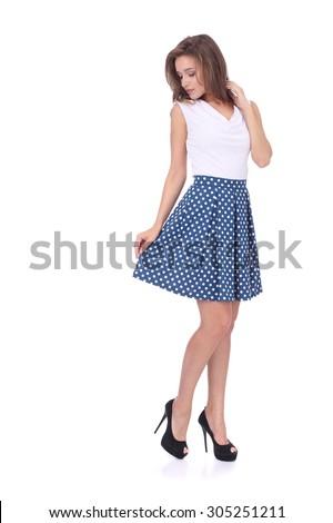 pretty young girl wearing blue short polka dot skirt - stock photo