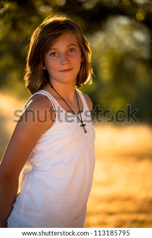 Pretty young girl wearing cross necklace - stock photo