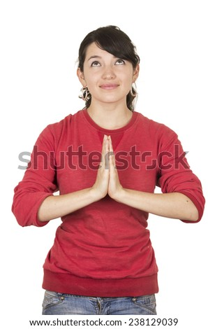 pretty young girl wearing red top posing looking up with palms together gesturing praying isolated on white - stock photo