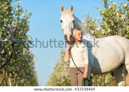 Pretty young girl with a white horse in blooming garden. - stock photo